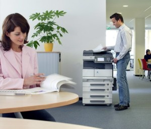 woman reading and man working on a printer in an office