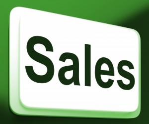 """""""sales"""" written on a sign with green background"""