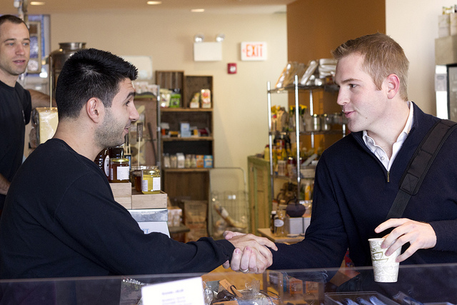 A customer shaking hands to a bartender