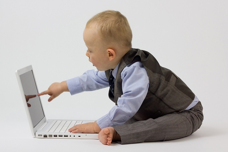 baby playing with a laptop